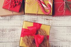 Redhead hairy legs dog holding Christmas gift box on white wooden background. top view stock images
