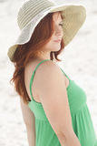 Redhead in hat. A redhead woman wearing a large sun hat at the beach Stock Images