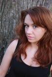Redhead hermoso cerca de un árbol, atractivo Fotografía de archivo libre de regalías