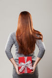 Redhead hiding a gift behind her back Royalty Free Stock Image