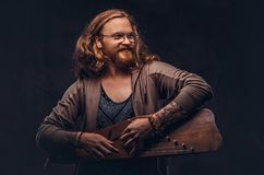 Redhead hipster male with long luxuriant hair and full beard dressed in casual clothes playing on a Russian traditional royalty free stock photo