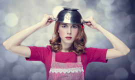Redhead housewife with colander over head Royalty Free Stock Image