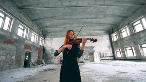 Redhead lady is playing the violin in an abandoned building. 4K stock video