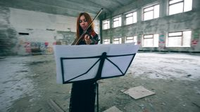 Redhead lady is playing the violin in a stranded building stock video