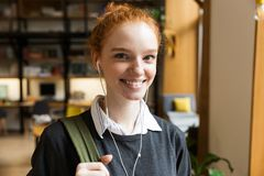 Redhead lady student posing indoors in library istening music with earphones. Image of beautiful redhead lady student posing indoors in library istening music royalty free stock photo