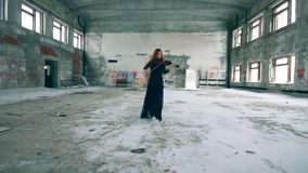 Redhead lady is walking along the hall while playing the violin stock footage