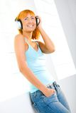 Redhead Listening To Music Stock Photo