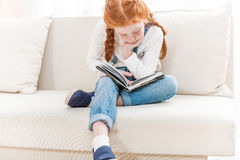 Redhead little girl sitting on sofa and reading book Stock Image