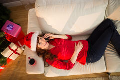 Redhead lying on the couch phoning at christmas Royalty Free Stock Photo