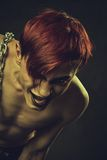 Redhead mad boy. Redhead naked young man with chains over dark background royalty free stock image