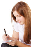 Redhead makes notes sideview Royalty Free Stock Images