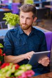 Redhead male using a tablet PC at the table. Portrait of bearded redhead male using a tablet PC at the table Stock Photography