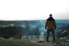 Man stands near an extinct campfire. Redhead man in a brown-and-blue windbreaker stands back to camera near an extinct fire, from which there is still smoke, on stock photography