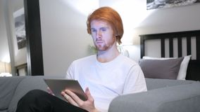 Redhead Man Browsing Internet on Tablet PC, Sitting on Couch. 4k , high quality stock footage