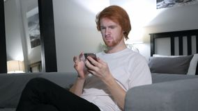 Redhead man browsing on smartphone, using internet. 4k , high quality stock video footage
