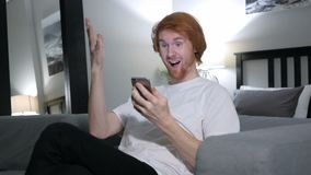 Redhead man excited for success while using smartphone. 4k , high quality stock video footage