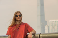 Redhead Man looks forwards. Man with long Hair Waiting on Central Pier in Hong Kong Royalty Free Stock Images
