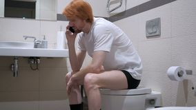 Redhead Man Talking on Phone in Toilet, Commode. 4k , high quality stock video