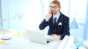 Redhead Man Talking on Phone at Work, Freelancer Desginer. 4k , high quality Royalty Free Stock Image