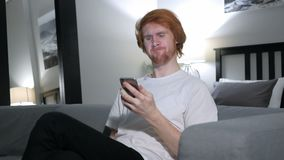 Redhead man upset for loss while using smartphone. 4k, high quality stock video