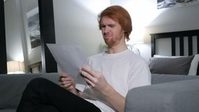 Redhead man upset after reading documents, feeling sad. 4k , high quality stock footage