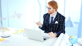 Redhead Man Using Smartphone for Online Browsing, Designer. 4k , high quality royalty free stock photography