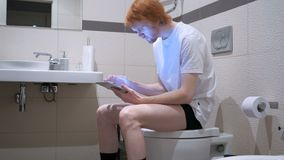Redhead man using tablet in bathroom, commode. 4k , high quality stock video