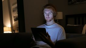 Redhead man using tablet computer at night. 4k , high quality stock video footage
