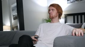 Redhead man watching tv, changing channels with remote. 4k , high quality stock footage