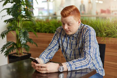 A redhead man wearing elegant shirt sitting at wooden table holding mobile phone being surprised while reading news online. An ast Royalty Free Stock Photos