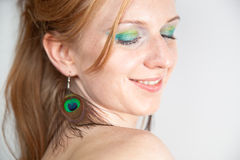 Redhead model with peacock ear-rings Stock Photos