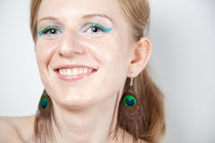 Redhead model with peacock ear-rings Royalty Free Stock Image