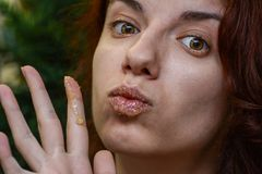 Lip scrub. Redhead model using a homemade lip scrub made out of honey, sugar and olive oil Stock Image