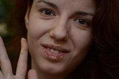 Lip scrub. Redhead model using a homemade lip scrub made out of honey, sugar and olive oil Stock Photo