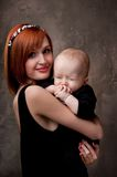 Redhead mother holding her sleepy baby boy Royalty Free Stock Photos