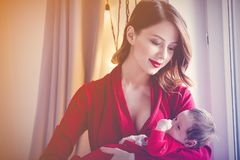 Redhead mother with new born child in red. Home location royalty free stock images