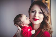 Redhead mother with new born child in red. Home location stock photo
