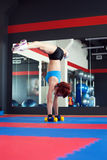 Redhead muscled female athlete does handstand Royalty Free Stock Photography