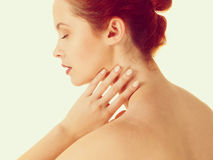 Redhead naked woman touching her neck. Nudity, beauty, skin and body care concept. Redhead woman touching her neck with her eyes closed. Studio shot isolated Royalty Free Stock Photography