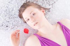 Redhead no gelo com pétala cor-de-rosa Fotografia de Stock Royalty Free
