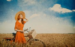 Girl with bicycle on wheat field. stock images