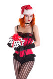 Redhead pinup girl in red corset and Santa Claus hat, holding gi Royalty Free Stock Photo