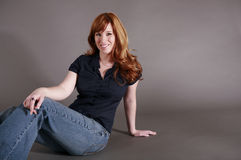 Redhead posing. Attractive redhead wearing blue blouse and jeans sitting on gray backdrop Royalty Free Stock Photos
