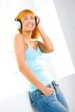 Redhead que escucha la música Foto de archivo
