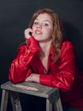 Redhead in Red Shirt Smiles. Beautiful young redhead smiling and posing for the camera Royalty Free Stock Image