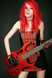 Redhead rocker girl with bass guitar Stock Images