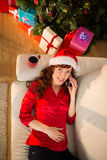 Redhead in santa hat lying on the sofa phoning Stock Image