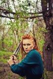 Redhead scandinavian woman. Redhead serious scandinavian woman posing with sword in a wood stock image