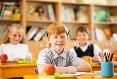 Redhead schoolboy behind desk Royalty Free Stock Image