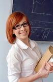 Redhead schoolgirl in front of blackboard Royalty Free Stock Images